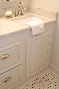 Polished chrome, Carrera marble, rectangular under-mount sink, white cabinets, basket weave marble mosaic.