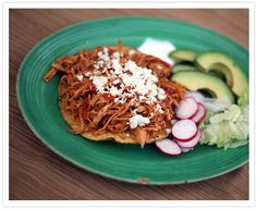 Tinga- shredded chicken in a tomato and chipotle sauce. It is one of my favorite tostada toppings!