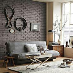dark brick accent wall with warm interior furnishings, hardwood floors, lots of light