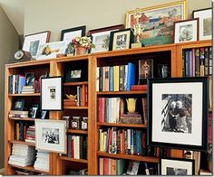 frames hung on the shelves and layered along the top