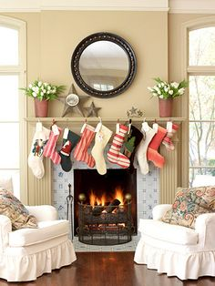 motley assortment of xmas stockings hanging from mantel and identified w classic xmas tags. hang group from bookshelf ledge or stairway banister if there isnt a mantel. these stockings are hanging from sm inconspicuous nails rather than stocking hangers