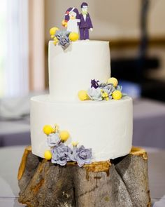 A lemon cake topped with an edible cartoon version of the bride and groom