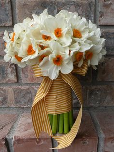 I love the pop of orange in the flowers combined with the striped ribbon.  If I did a spring wedding