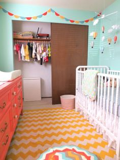 A colorful boy's nursery uses bright accents to pop against a more serene turquoise wall paint.