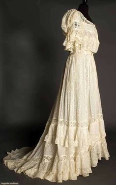 "IVORY LAWN & LACE TEAGOWN, c. 1905  Pin-tucked cotton woven w/ serpentine-dot pattern, embroidered lace inserts at waist & short sleeves, Val lace trim, trained skirt, ivory China silk lining, B 40"", W 30"", L 63""- 76"", (silk ribbons missing from insertion lace, few tiny brown spots CF bodice, CF hooks & eyes loose) excellent. Brooklyn Museum"