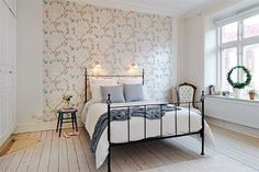Uncluttered bedroom with just enough wallpaper and bleached wood floors
