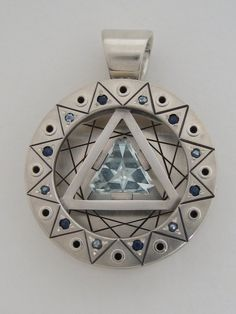 Andy Lucas - This new pendant is a custom creation.  The center stone is an Aquamarine cut by David Brackna.  He calls this cut his turkish star.  The accent stones on the face are Aquamarine and Sapphire.  The face and both sides of the back plate have been engraved. This 12-pointed geometry is made of 4 triangles shows how squares and triangles can interrelate.  Look for the squares within the triangles.  Enjoy!