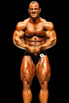 Buff Bodybuilder Flexes His Muscles For The Judges