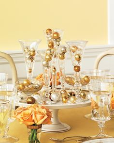 Ball-shaped ornaments displayed in glass flutes mimic bubbling glasses of Champagne -- gather flutes in varying styles, and cluster them on a cake stand for a glamorous centerpiece