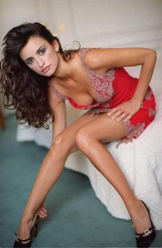 Penelope Cruz sorting her heels out on the bed in a slip