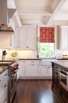 White kitchen with dark wood floors- so pretty!  And I love the red window treatment too.