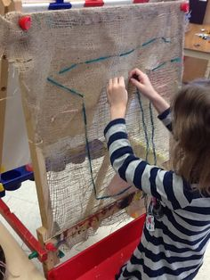 Weaving on burlap on easel-remove part of easel creates a frame for burlap-Play; in a new way.