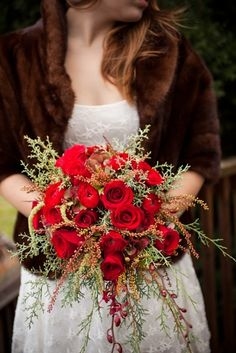 Red roses add a glam touch at a rustic winter wedding.