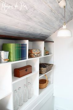 Whitewashed attic ceiling with built-in shelving along stairs