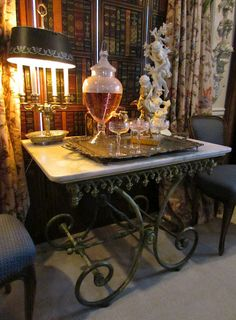 Curtains, lamp, books, silver tray, old French pastry table....great presentation