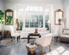 Living Room Photo - Upholstered furniture and gilded mirrors in a white-walled living space