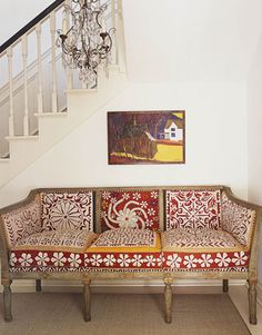 Graphic red and white Suzanis give an antique Swedish sofa from Indigo Seas a buoyant, modern look.