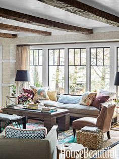 Living room in a lake house. Design: Thom Filicia. housebeautiful.com. #lake_house #living_room #sofa #wood_beams.  Like the beams and windows