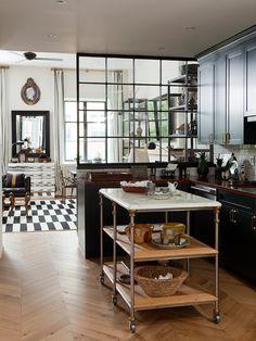 black cabinets, brass hardware, herringbone wood floor, island, divided light window room divider