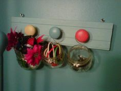 Found this idea on here a while back while re-doing daughter's room...used small jars (pimento jars), looped wired around & tied to old knobs (re-painted from dresser we were re-doing)...put on scrap, painted wood...used to hold ponytail holders, bobby pins, etc