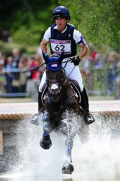 Phillip Dutton of the United States riding Mystery Whisper through a water jump in the Eventing Cross Country Equestrian event. Dutton (11th) is the top U.S. rider.
