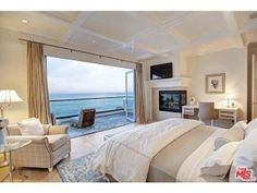 A master bedroom with a creme color scheme. It features a fireplace, a work space, seating area, and beautiful blue ocean views.  Malibu, CA Coldwell Banker Residential Brokerage $15,900,000
