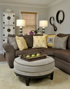 small living room, yellow pillows, round ottoman, double lamps, window