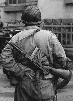 A Marine armed with an M1A1 Thompson submachine gun and a .45 caliber Colt-type pistol