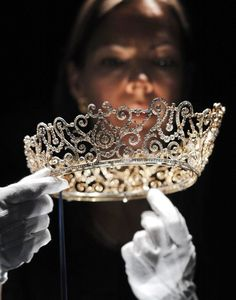 Curator Caroline de Guitaut, holds the Delhi Durbar Tiara, on show for the first time and made to mark the succession of King George V as King Emperor in 1911. The new exhibition at Buckingham Palace shows jewels collected by six monarchs over three centuries to mark the Queen's Diamond jubilee this summer.