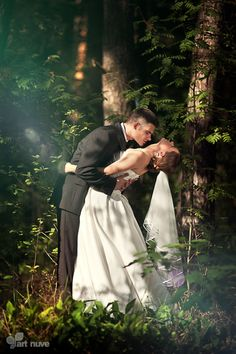 Wedding Photos - Groom kissing the bride in the woods
