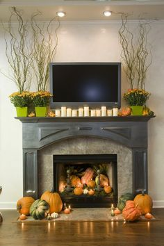 #Fall #fireplace #decor #ideas — love the #pumpkins and #candles spilling out of the fireplace with the #flowers on the #mantle - great combination!
