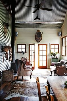 Polished timber boards, animal trophy head, ceiling fan with 16 ft ceilings, cow skin rug, mismatched furnishings, french doors and corrugated iron.