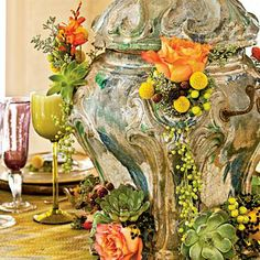 Create a Showpiece | Tuck stems of roses, succulents, pepper berry, and eucalyptus into the holes of an 18th-century glazed ceramic French brazier for a dramatic cascading effect. | SouthernLiving.com