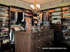 Andrea Guerriero - DRE DESIGNS www.dredesigns.ca www.facebook.com/dredesigns.ca  Custom designed walk-in closet.  We turned a bedroom into a change room, complete with large mirror on the wall to the right, to the left is an actual closet with more storage that is shelving for shoes, there is a chair and ottoman in this space, and of course the island and small chandelier. Looks great and has storage galore!