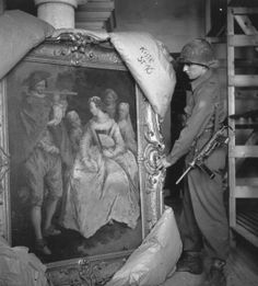 May 1945: A US Army soldier unwraps an old master painting by the 18th century painter Fragonard. This along with other art treasures was found at Neuschwanstein Castle, Fussen, Germany, where the Nazis kept treasures stolen from throughout Europe during the Second World War. (Photo by Horace Abrahams/Keystone/Getty Images)