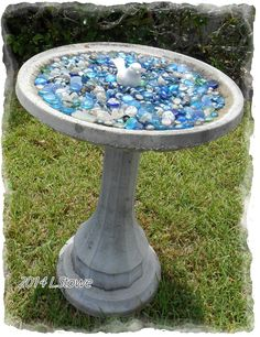 Several bags of dollar store glass stones + a dollar store bird figurine = adorable birdbath. The blue stones look great even when the water dries up. 2014 L.Stowe