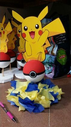 "Pokémon party centerpieces. I bought the 4"" balls at Walmart  and hand paint the red and the black. The Pikachu I just print it on hard paper and cut it and I used the glue gun to put everything together as you can see in the background."