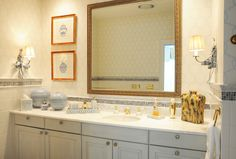 Beautiful renovated in-suite bath with custom marble mosaic and marble counter. Custom frame material was used to create the mirror. Faux finishes were added to give warmth to the room.  Photo by Janine Menlove.