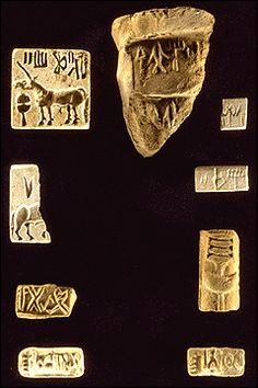 A collection of inscribed objects found along the main street leading to the southern gateway of Mound E at Harappa. The fragmentary seal on the left is the earliest seal found to date, and depicts a bovine carved in a very archaic style. At the top center is a terra cotta sealing with two seal impressions. This sealing may have been used to close a large jar full of trade goods such as oil.  Harappa Archaeological Research Project.