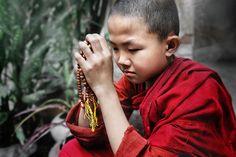 A young novice (monk) meditating with prayer beads, Myanmar - David Lazar, photographer