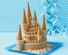 """Towering Sand Castle Cake- This crumb-covered cake is """"shore"""" to make a splash at any beach- or sea-themed birthday bash. Scatter some candy seashells and rocks around the base and prepare for a wave of compliments."""