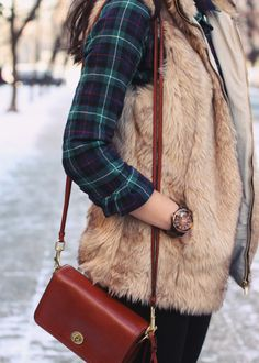 Plaid top with fur vest and small cross body leather purse.