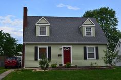 Seamless steal siding in sage green with a red front door and black shutters.