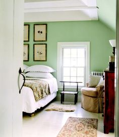 Soft green walls and a white-painted floor give the master bedroom in this Connecticut farmhouse a soothing appearance.