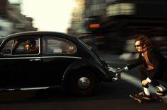Skateboarding behind a VW Beetle Black