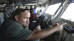 Navy harbor pilot explains to his 9-year-old son James how the USS Ronald Reagan is steered while in the navigation bridge during a public tour of the nuclear powered aircraft carrier docked at North Island in San Diego on Saturday. Hayne Palmour IV