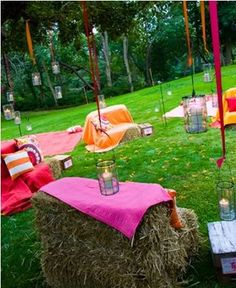 Budget outdoor lounge made with hay bales, colored cloths and colored streamers holding candles