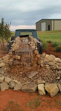 Rustic, western yard decor. Old pickup waterfall. Large mountain rocks and???