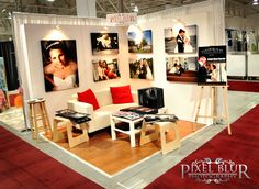 simple elegant booth - love the sofa / pillows (homey look)... and the selection of images on wall - practical? no place to display brochures, TV / monitor for slideshow; laptop, etc