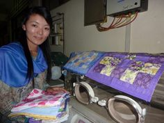 AnJi Sherpa of OHW Nepal, showing some of the beautiful premature baby blankets for use in the humidicribs in Paropakar Maternity Hospital NICU in Kathmandu, Nepaldonated by Coorparoo Quilters.